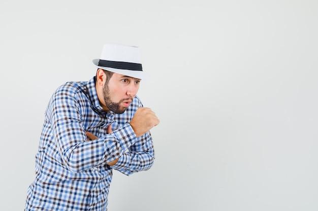Giovane maschio soffre di tosse in camicia a quadri, cappello e sembra a disagio. vista frontale.