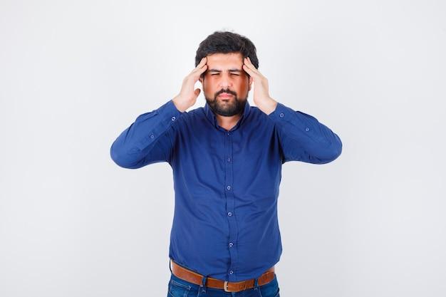 Giovane maschio che soffre di mal di testa in camicia blu e sembra stanco. vista frontale.