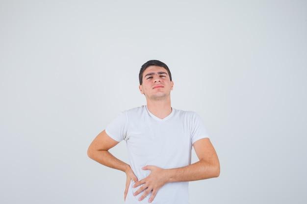Tシャツで肝痛に苦しんでいる若い男性と痛みを伴う、正面図。