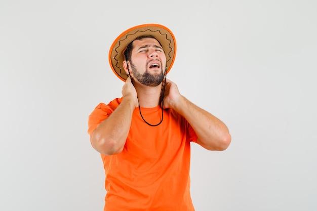 オレンジ色のtシャツ、帽子、疲れているように見える、正面図で首の痛みに苦しんでいる若い男性。