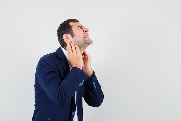 Молодой мужчина страдает от боли в шее в рубашке, куртке и выглядит усталым