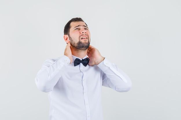 흰 셔츠에 목 통증으로 고통 받고 피곤한 젊은 남성. 전면보기.