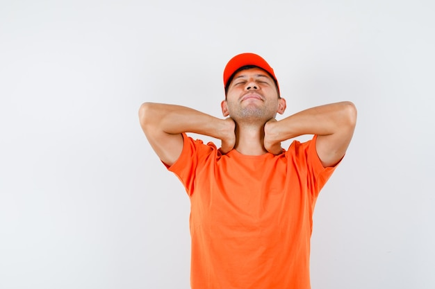 Young male suffering from neck pain in orange t-shirt and cap and looking fatigued