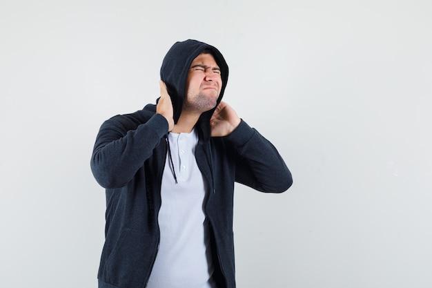 Giovane maschio che soffre di dolore al collo in t-shirt, giacca e sembra stanco. vista frontale.