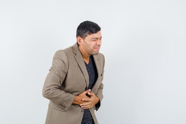 灰色がかった茶色のジャケットで腹痛に苦しんでいて、不快に見える若い男性。正面図。あなたのテキストのための空きスペース