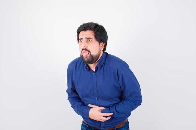 青いシャツの腹痛に苦しんでいる若い男性と体調不良、正面図。