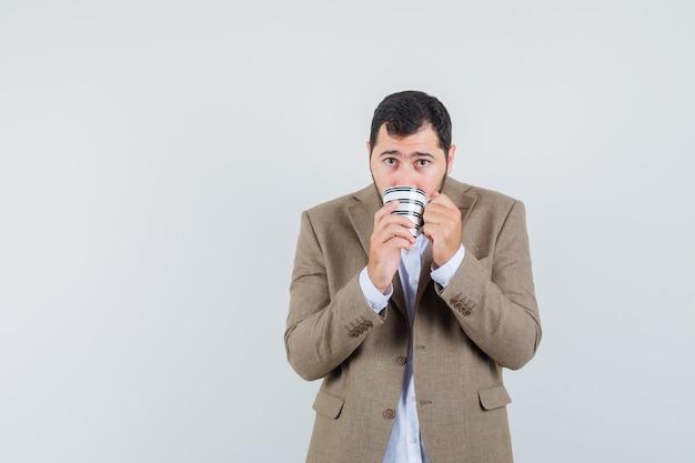 Giovane maschio in vestito che beve caffè e che sembra spaventato, vista frontale.