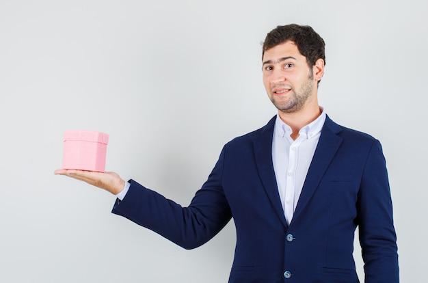 Giovane maschio in vestito che tiene confezione regalo e guardando allegro, vista frontale.
