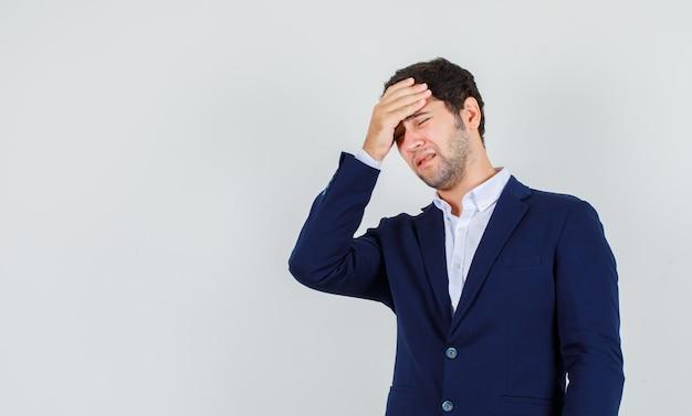 Giovane maschio in tuta tenendo la mano sulla testa e guardando doloroso, vista frontale.