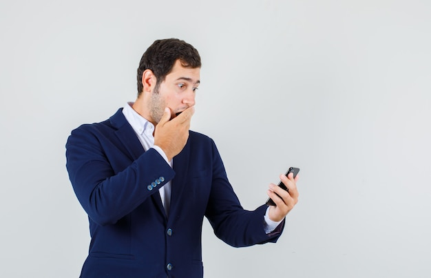 Young male in suit looking at smartphone with hand on mouth and looking shocked , front view.
