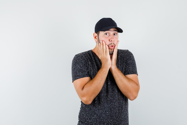 Young male in t-shirt and cap holding hands on cheeks and looking surprised