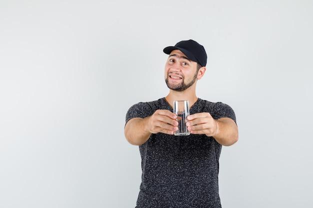Giovane maschio in maglietta e berretto che offre un bicchiere d'acqua e sembra amichevole