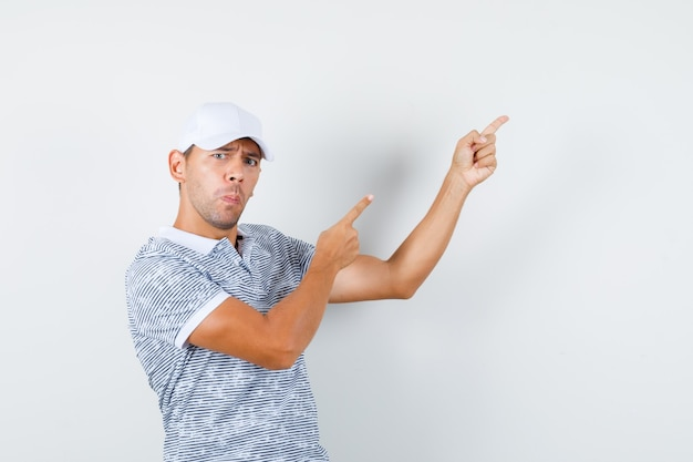 Young male in t-shirt and cap pointing fingers up and looking curious