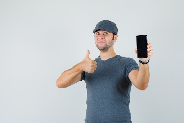 Young male in t-shirt cap showing thumb up while holding mobile phone