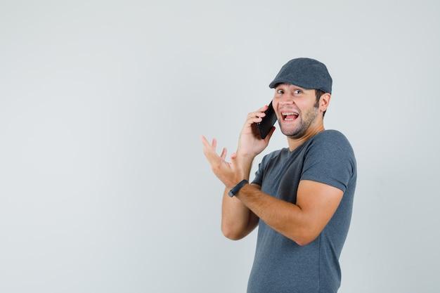 Giovane maschio in protezione della maglietta che parla sul telefono cellulare e che sembra felice