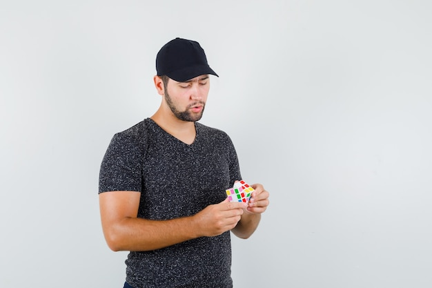 Young male in t-shirt and cap trying to solve rubik's cube and looking pensive