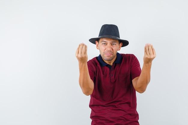 Giovane maschio in t-shirt, cappello che fa gesto italiano, vista frontale.