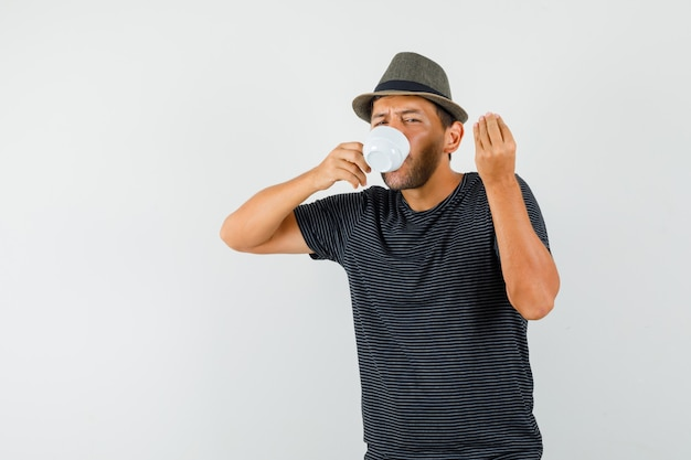 Young male in t-shirt hat drinking coffee doing italian gesture and looking delighted