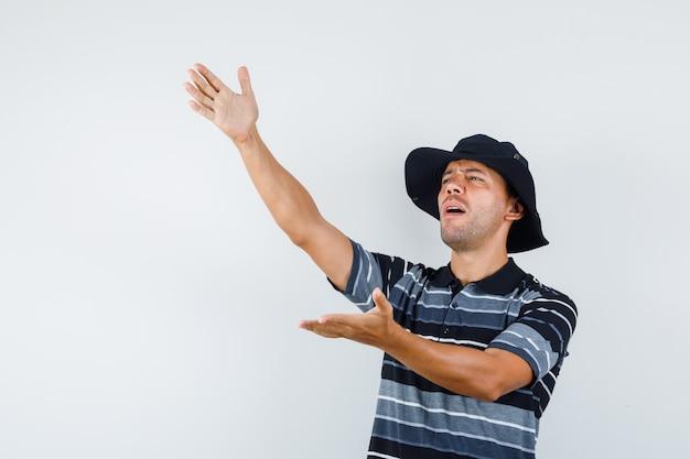 Giovane maschio in maglietta, cappello che dà istruzioni gridando e guardando interessato, vista frontale.