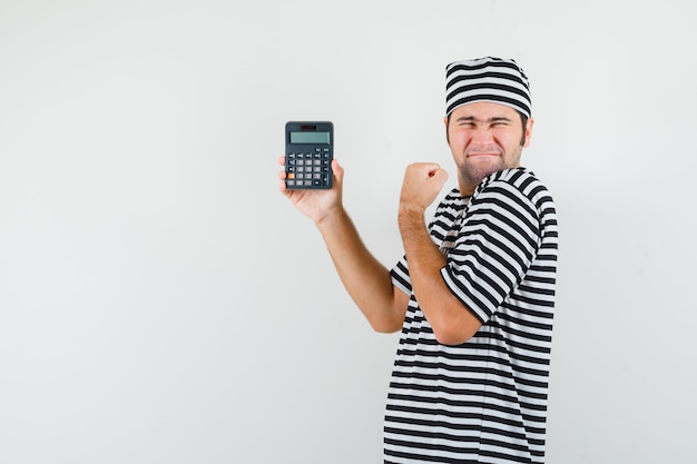 Young male in t-shirt, hat holding calculator and looking blissful .