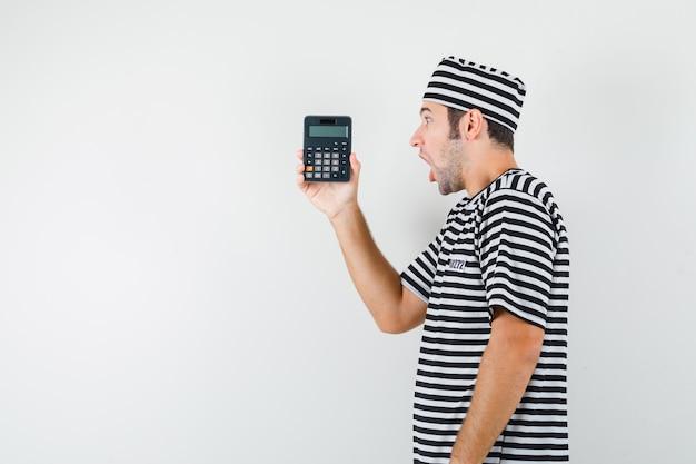 Giovane maschio in t-shirt, cappello guardando la calcolatrice e guardando meravigliato.