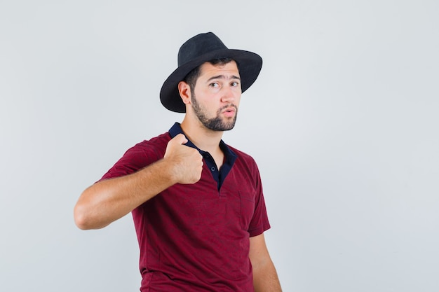 Young male in t-shirt,hat pointing at himself and looking uncomfortable , front view.