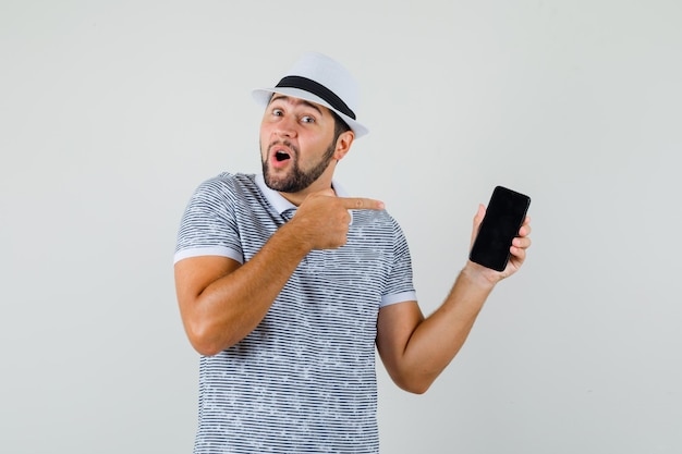 Young male in t-shirt, hat pointing at mobile phone and looking amazed , front view.
