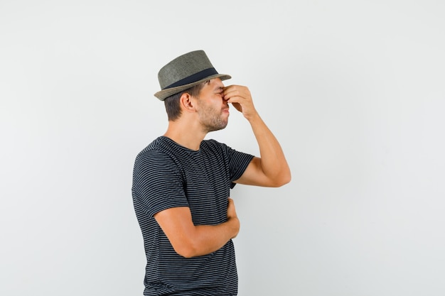 Young male in t-shirt hat rubbing eyes and nose and looking exhausted
