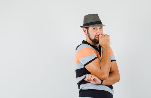 Giovane maschio in t-shirt, cappello in piedi nella posa di pensiero e guardando a disagio, vista frontale.