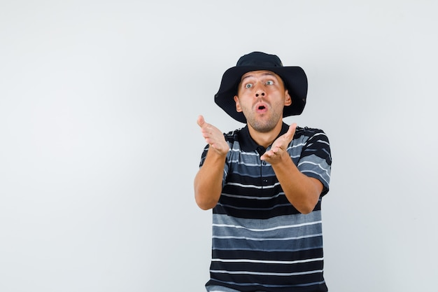Giovane maschio in t-shirt, cappello cercando di spiegare qualcosa e guardando eccitato, vista frontale.
