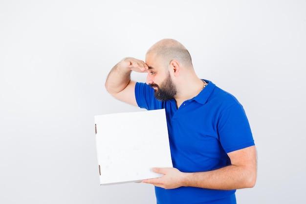 Giovane maschio in t-shirt tenendo la mano sulla fronte e guardando domandato, vista frontale.