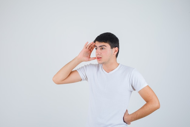 Giovane maschio in t-shirt tenendo la mano sopra la testa e guardando concentrato, vista frontale.