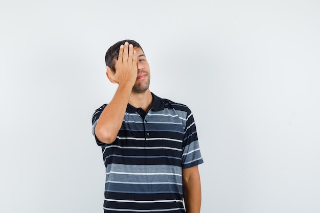Giovane maschio in maglietta che tiene la mano su un occhio e sembra allegro, vista frontale.