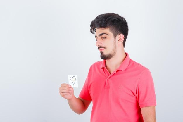 Giovane maschio in maglietta che tiene una nota adesiva mentre distoglie lo sguardo e sembra pensieroso, vista frontale.