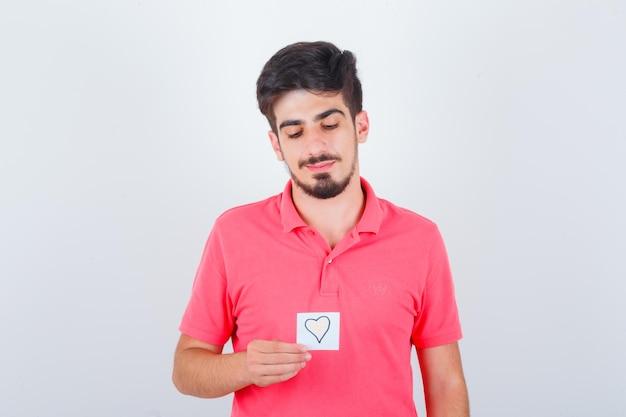 Giovane maschio in maglietta che tiene una nota adesiva mentre guarda in basso e sembra speranzoso, vista frontale.