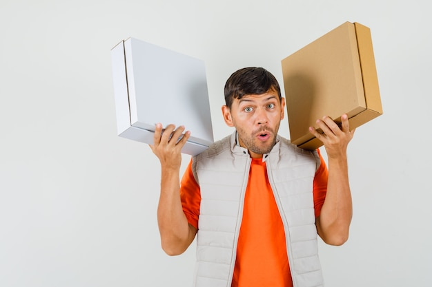 Young male in t-shirt, jacket holding cardboard boxes and looking amazed , front view.