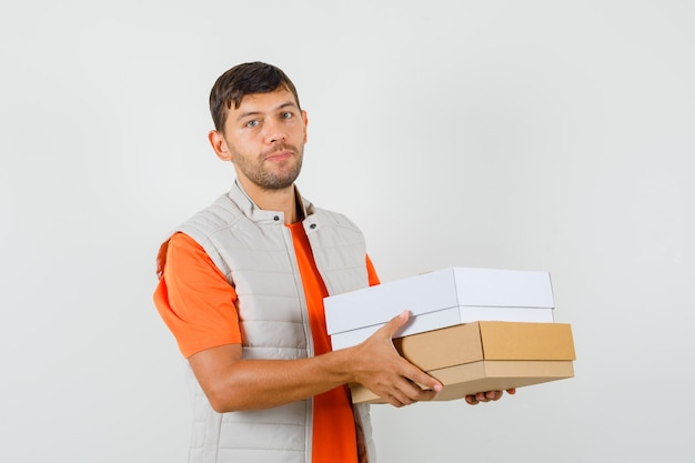 Young male in t-shirt, jacket holding cardboard boxes and looking sensible , front view.
