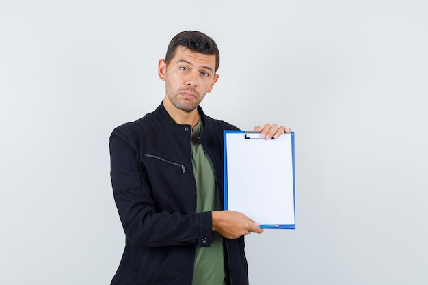 Young male in t-shirt, jacket holding clipboard and looking sensible , front view.