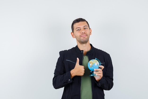 Young male in t-shirt, jacket holding globe with thumb up and looking pleased , front view.