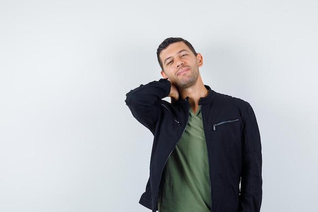 Young male in t-shirt, jacket holding hand on neck and looking handsome , front view.