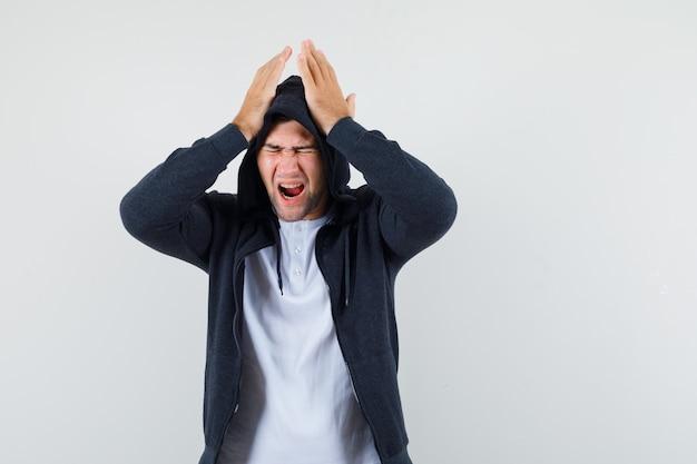 Giovane maschio in t-shirt, giacca tenendo le mani sulla testa e guardando dispiaciuto, vista frontale.