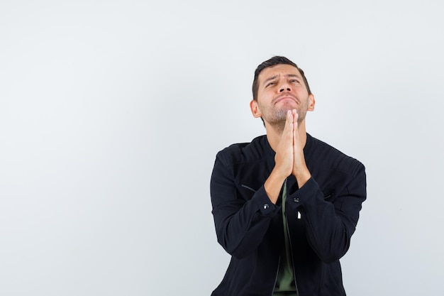 Young male in t-shirt, jacket holding hands in praying gesture and looking hopeful , front view.