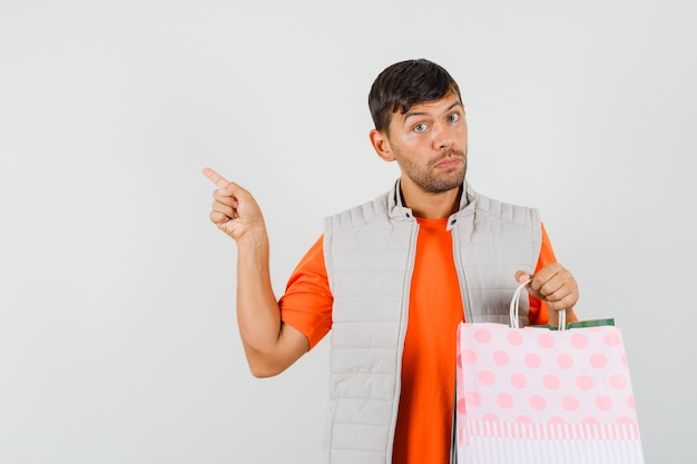 Giovane maschio in t-shirt, giacca tenendo le borse della spesa, indicando lontano, vista frontale.