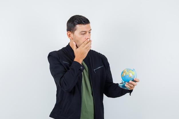 Young male in t-shirt, jacket looking at globe and looking wondered , front view.