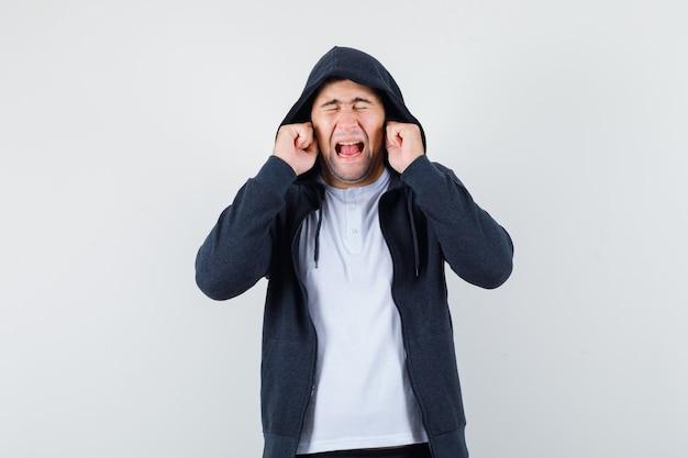 Giovane maschio in t-shirt, giacca tappando le orecchie con le dita e guardando infastidito, vista frontale.