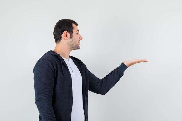 Giovane maschio in t-shirt, giacca fingendo di tenere qualcosa e guardando concentrato, vista frontale.