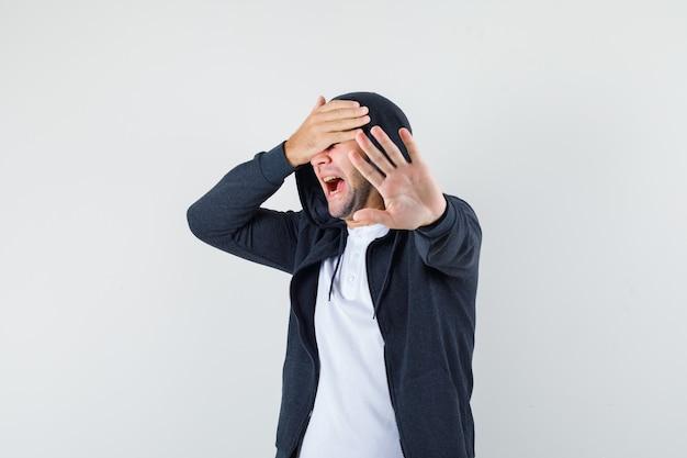 Giovane maschio in t-shirt, giacca che mostra il gesto di arresto e sembra spaventato, vista frontale.