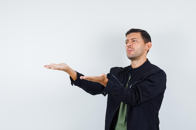 Young male in t-shirt, jacket stretching hands in disapproval gesture and looking downcast , front view.