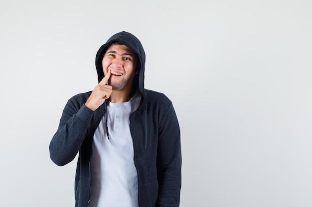 Giovane maschio in t-shirt, giacca che soffre di mal di denti e sembra a disagio, vista frontale.