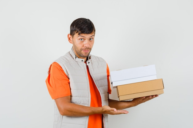 Young male in t-shirt, jacket welcoming and holding cardboard boxes , front view.